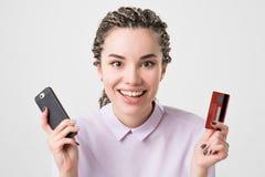 Mujer joven europea caucásica feliz que sostiene el teléfono y tarjeta que hace orden en línea Foto de archivo libre de regalías
