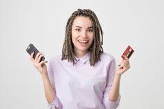 Mujer joven europea caucásica feliz que sostiene el teléfono y tarjeta que hace orden en línea Imágenes de archivo libres de regalías