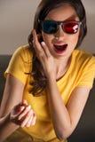 Mujer joven expresiva que mira la película 3d Fotografía de archivo