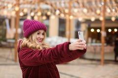 Mujer joven expresiva que toma el autorretrato en el teléfono móvil Foto de archivo libre de regalías