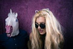Mujer joven extraña en gafas de sol y oídos del gatito que besa unicornio feliz imagen de archivo