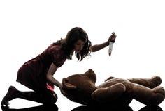 Mujer joven extraña que mata a su silueta del oso de peluche Foto de archivo libre de regalías