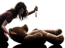 Mujer joven extraña que mata a su silueta del oso de peluche Imagen de archivo