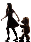 Mujer joven extraña y silueta viciosa del oso de peluche Fotografía de archivo