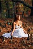 Mujer joven fantástica hada hermosa de la muchacha de la fantasía con el vestido largo blanco en parque ventoso del otoño Imagenes de archivo