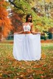 Mujer joven fantástica hada hermosa de la muchacha de la fantasía con el vestido largo blanco en parque ventoso del otoño Fotos de archivo libres de regalías