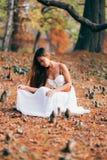 Mujer joven fantástica hada hermosa de la muchacha de la fantasía con el vestido largo blanco en parque ventoso del otoño Imagen de archivo