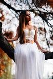 Mujer joven fantástica hada hermosa de la muchacha de la fantasía con el vestido largo blanco en parque ventoso del otoño Foto de archivo libre de regalías