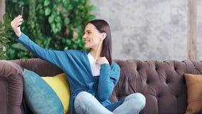 Mujer joven feliz adorable que tiene emociones positivas que presentan tomando el selfie almacen de video
