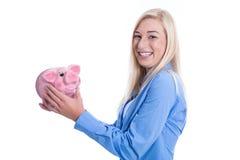Mujer joven feliz aislada con una hucha rosada. Fotos de archivo