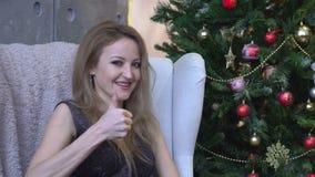 Mujer joven feliz alegre que muestra el pulgar para arriba en fondo del árbol de navidad metrajes