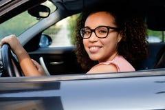 Mujer joven feliz asentada en su nuevo coche foto de archivo