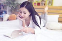 Mujer joven feliz asiática que lee un libro con la mentira en la cama y el tacto de su barbilla con la mano fotografía de archivo