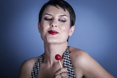 Mujer joven feliz atractiva con el lollypop en su boca en backg azul Fotos de archivo