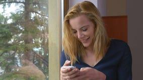 Mujer joven feliz atractiva que manda un SMS a un mensaje en la ventana metrajes