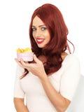 Mujer joven feliz atractiva que sostiene un pequeño cuenco de patatas a la inglesa de patata Imágenes de archivo libres de regalías