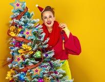Mujer joven feliz cerca del adornamiento del árbol de navidad Fotografía de archivo