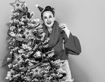 Mujer joven feliz cerca del adornamiento del árbol de navidad Fotos de archivo