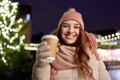 Mujer joven feliz con café en el mercado de la Navidad Imagen de archivo