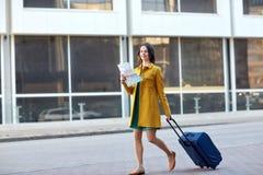 Mujer joven feliz con el bolso del viaje y mapa en ciudad Fotos de archivo