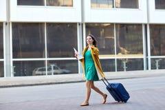 Mujer joven feliz con el bolso del viaje y mapa en ciudad Foto de archivo libre de regalías