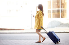 Mujer joven feliz con el bolso del viaje y mapa en ciudad Foto de archivo
