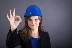 Mujer joven feliz con el casco de protección que muestra la muestra aceptable foto de archivo