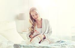 Mujer joven feliz con el cuaderno en cama en casa Imagen de archivo