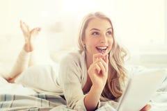 Mujer joven feliz con el cuaderno en cama en casa Fotos de archivo libres de regalías