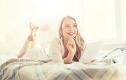 Mujer joven feliz con el cuaderno en cama en casa Fotografía de archivo