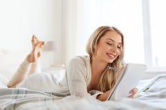 Mujer joven feliz con el cuaderno en cama en casa Foto de archivo libre de regalías
