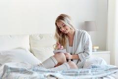 Mujer joven feliz con el cuaderno en cama en casa Imágenes de archivo libres de regalías