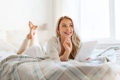 Mujer joven feliz con el cuaderno en cama en casa Imagenes de archivo