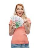 Mujer joven feliz con el dinero euro del efectivo Foto de archivo