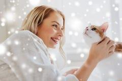 Mujer joven feliz con el gato en cama en casa Imagenes de archivo