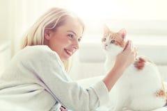 Mujer joven feliz con el gato en cama en casa Imagen de archivo libre de regalías