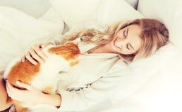 Mujer joven feliz con el gato en cama en casa Fotografía de archivo