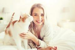 Mujer joven feliz con el gato en cama en casa Imágenes de archivo libres de regalías
