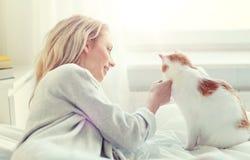Mujer joven feliz con el gato en cama en casa Foto de archivo