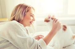Mujer joven feliz con el gato en cama en casa Fotos de archivo libres de regalías