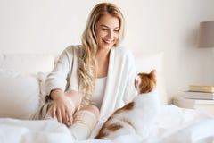 Mujer joven feliz con el gato en cama en casa Fotografía de archivo libre de regalías
