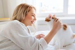 Mujer joven feliz con el gato en cama en casa Foto de archivo libre de regalías