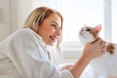 Mujer joven feliz con el gato en cama en casa Fotos de archivo
