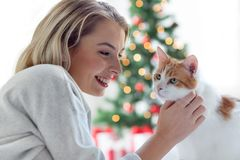 Mujer joven feliz con el gato en la Navidad Fotografía de archivo libre de regalías