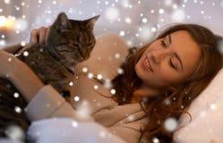 Mujer joven feliz con el gato que miente en cama en casa Imagen de archivo libre de regalías