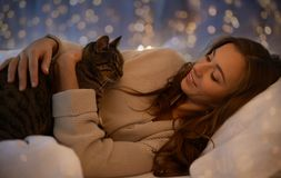 Mujer joven feliz con el gato que miente en cama en casa Imagen de archivo