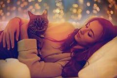 Mujer joven feliz con el gato que miente en cama en casa Fotografía de archivo libre de regalías