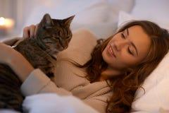 Mujer joven feliz con el gato que miente en cama en casa Fotografía de archivo