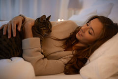 Mujer joven feliz con el gato que miente en cama en casa Imágenes de archivo libres de regalías