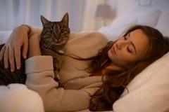 Mujer joven feliz con el gato que miente en cama en casa Fotos de archivo